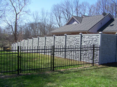 6 Foot Grey Granite Rock Wall Paired Next to 4 Foot Aluminum Fence